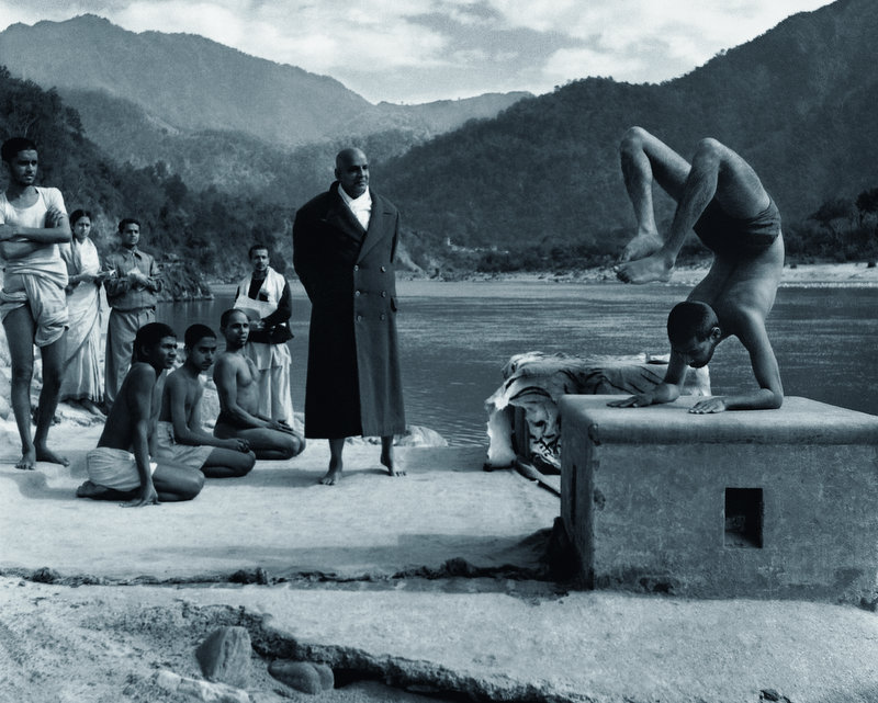 Master Sivananda watches Swami Vishnu-devananda demonstrate the Scorpion Asana in Rishikesh, Himalayas, circa 1950