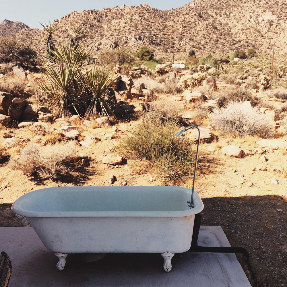 An outdoor bathtub at our home + cracks in the pavement from the heat.