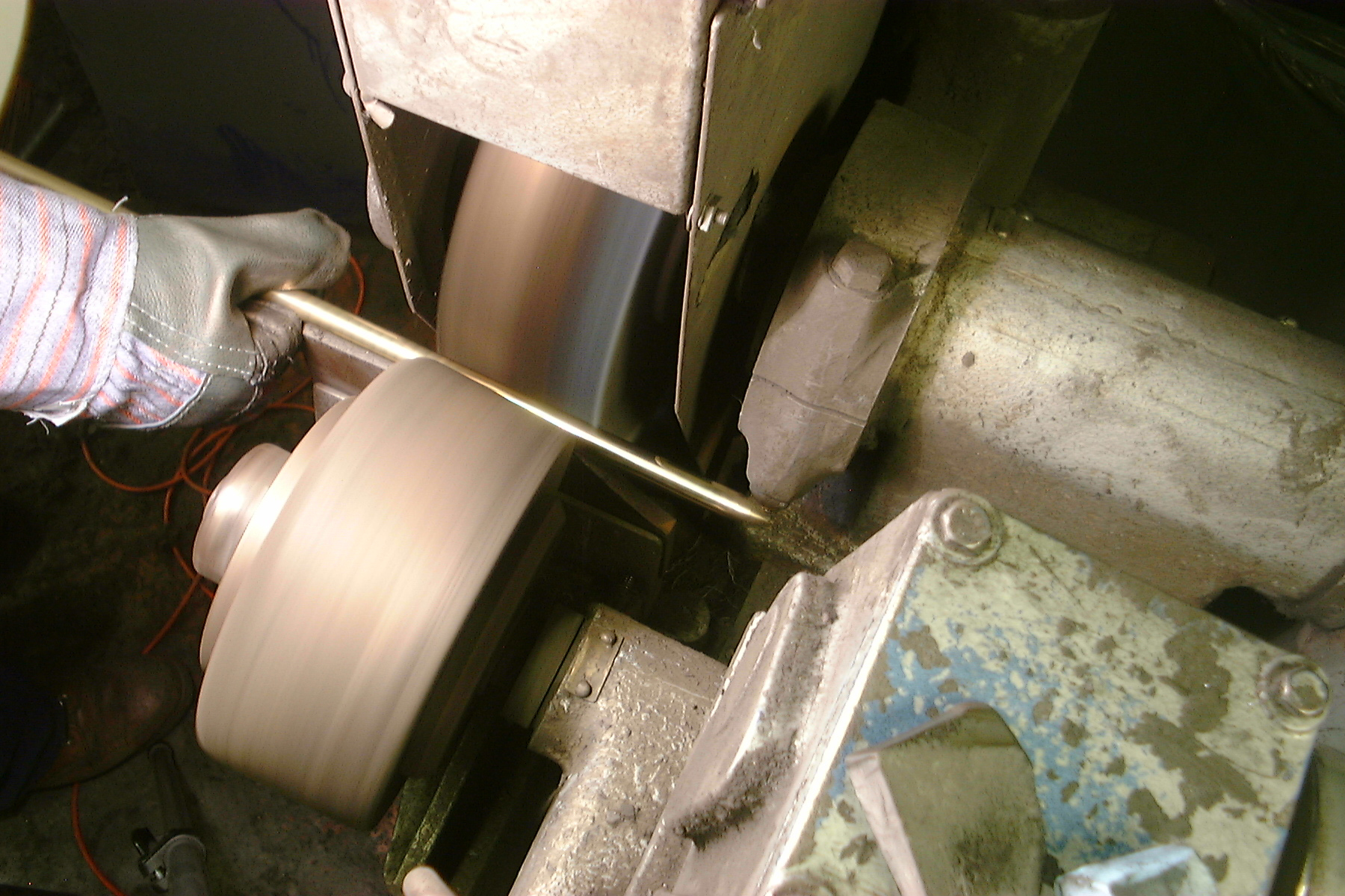 Brass stair rods being polished before applying lacquer.
