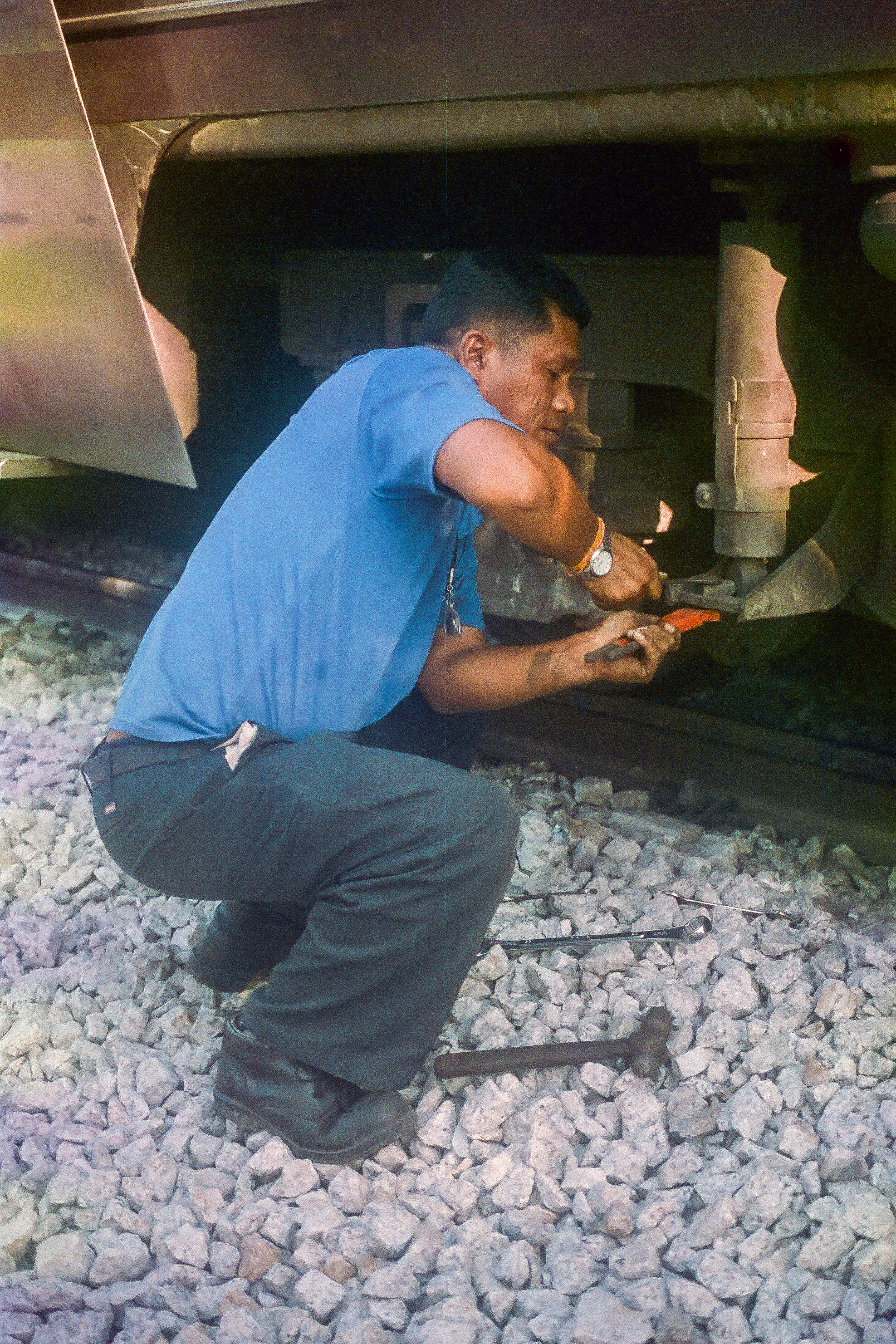 Conductor fixing the train on  the Georgetown to Chumphon route .