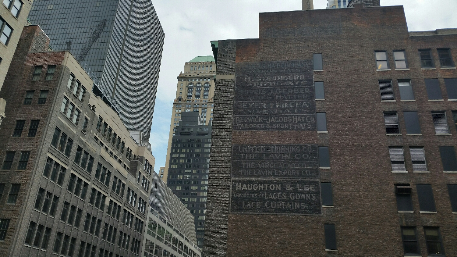 A view from our roof top , a list of defunct  businesses painted on the wall . These old advertisements  now serve as a memorial  to the old Millinery  District  .
