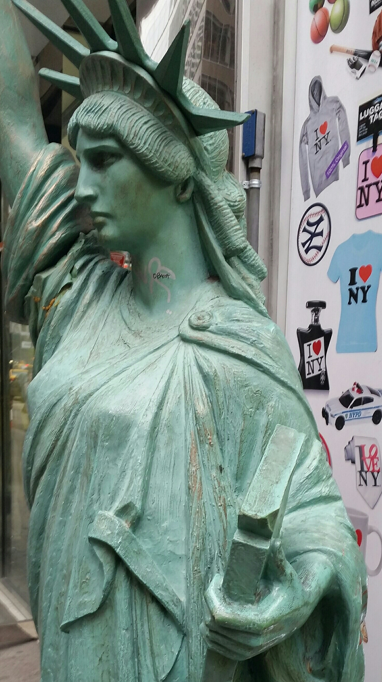 Lady Liberty doing her best in front of a souvenir  shop on 6th. Avenue .