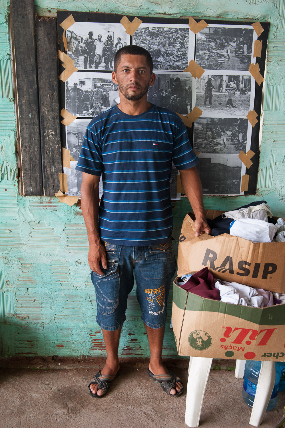 In February 2014, Jean Paulo Teixeina Silva and his family were forcibly evicted – without notice – from his home in the favela (slum) of Alto da Paz in Fortaleza, Brazil. Now homeless, he stands with the only belongings he could carry in front of images of the violent eviction.