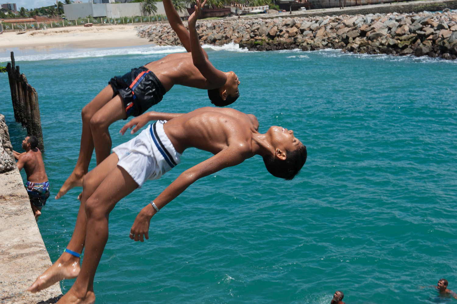 Boys and men compete to see who can do the best dive off of the seaside pier in Fortaleza.