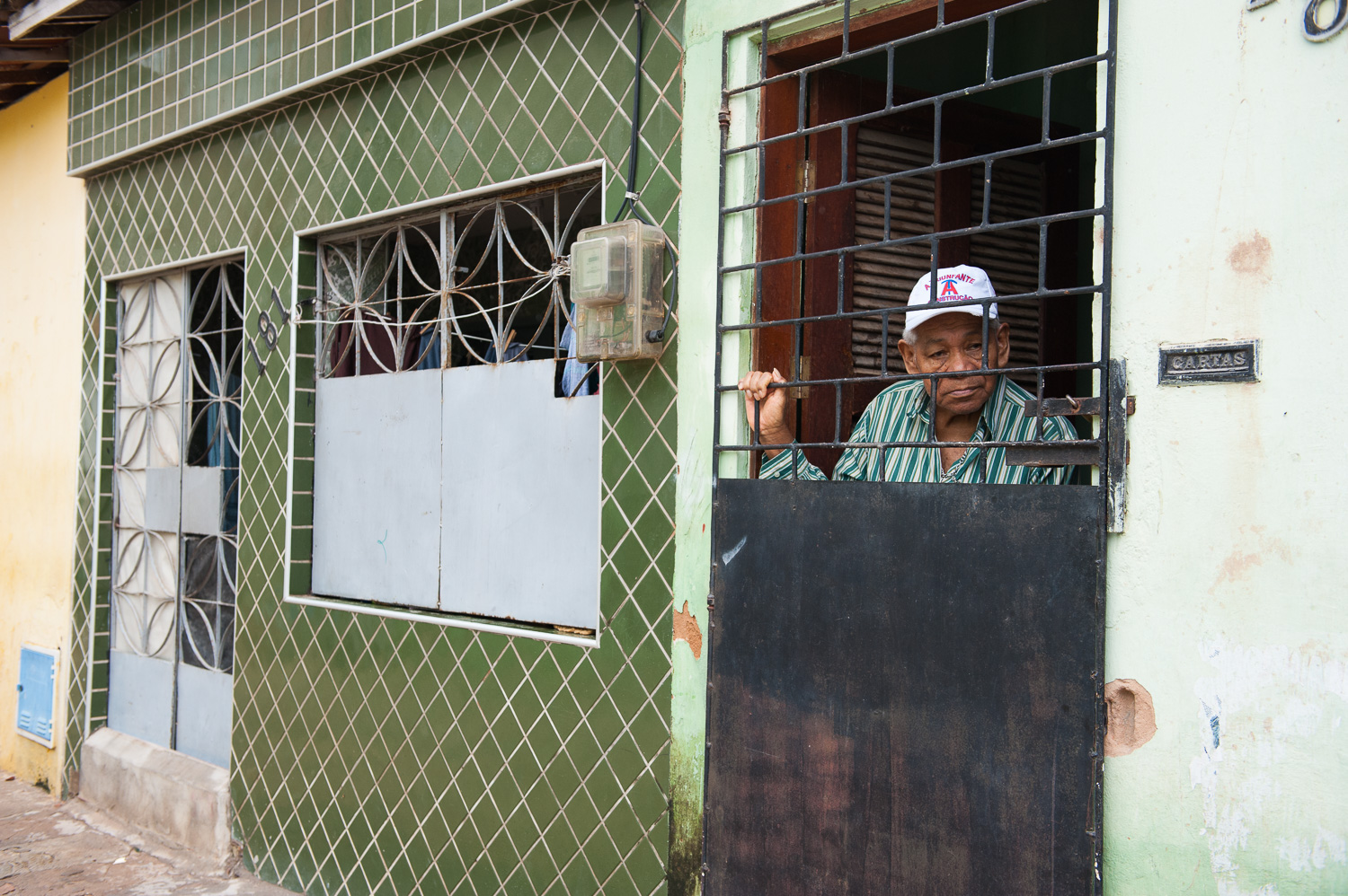 An elderly man who had been evicted from his home on the ocean looks out from his new home in the favela (slum) Poco da Draga, which may be demolished for a parking lot.
