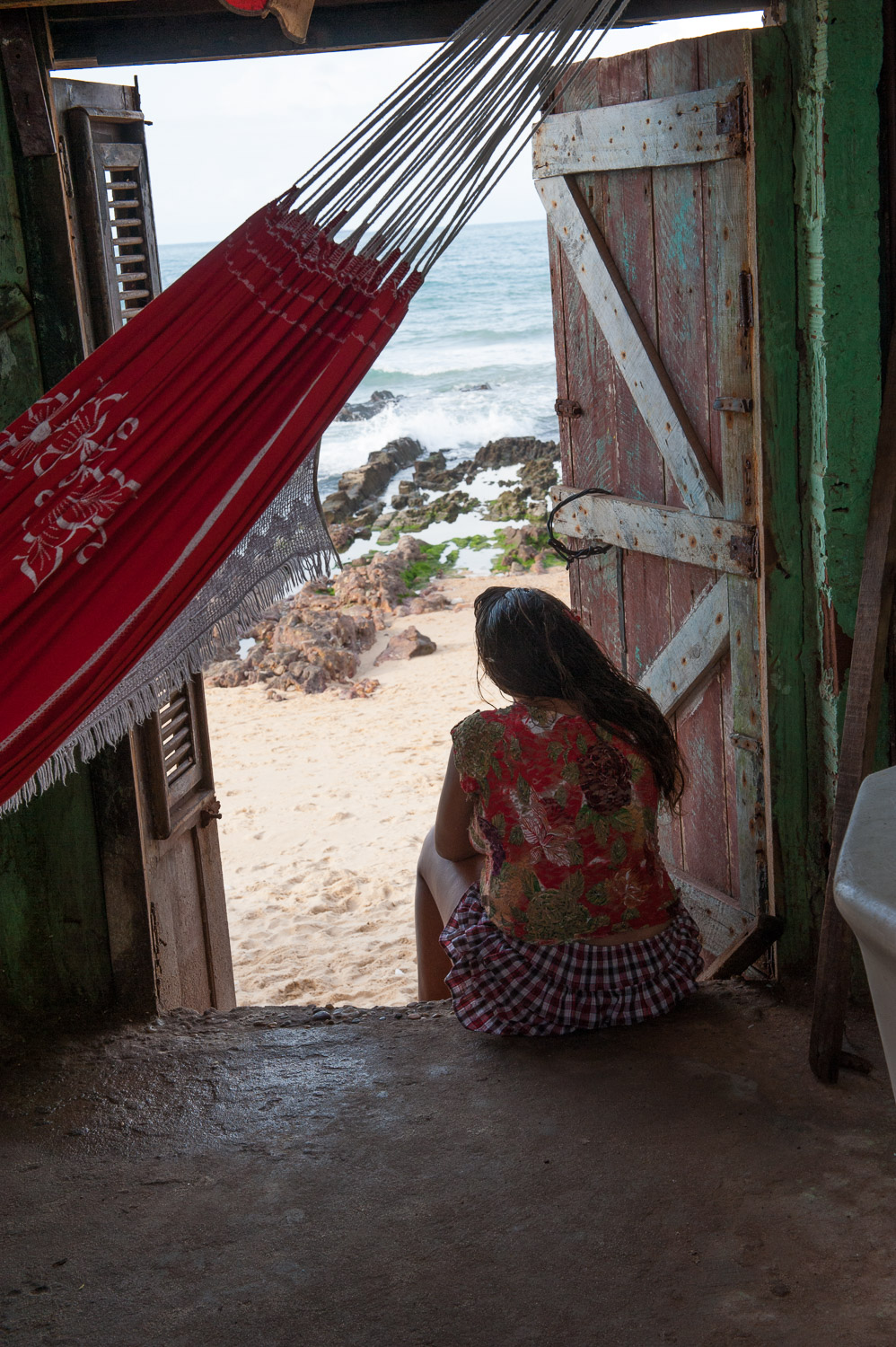 A favela (slum) resident of Fortaleza looks out at the Atlantic Ocean.