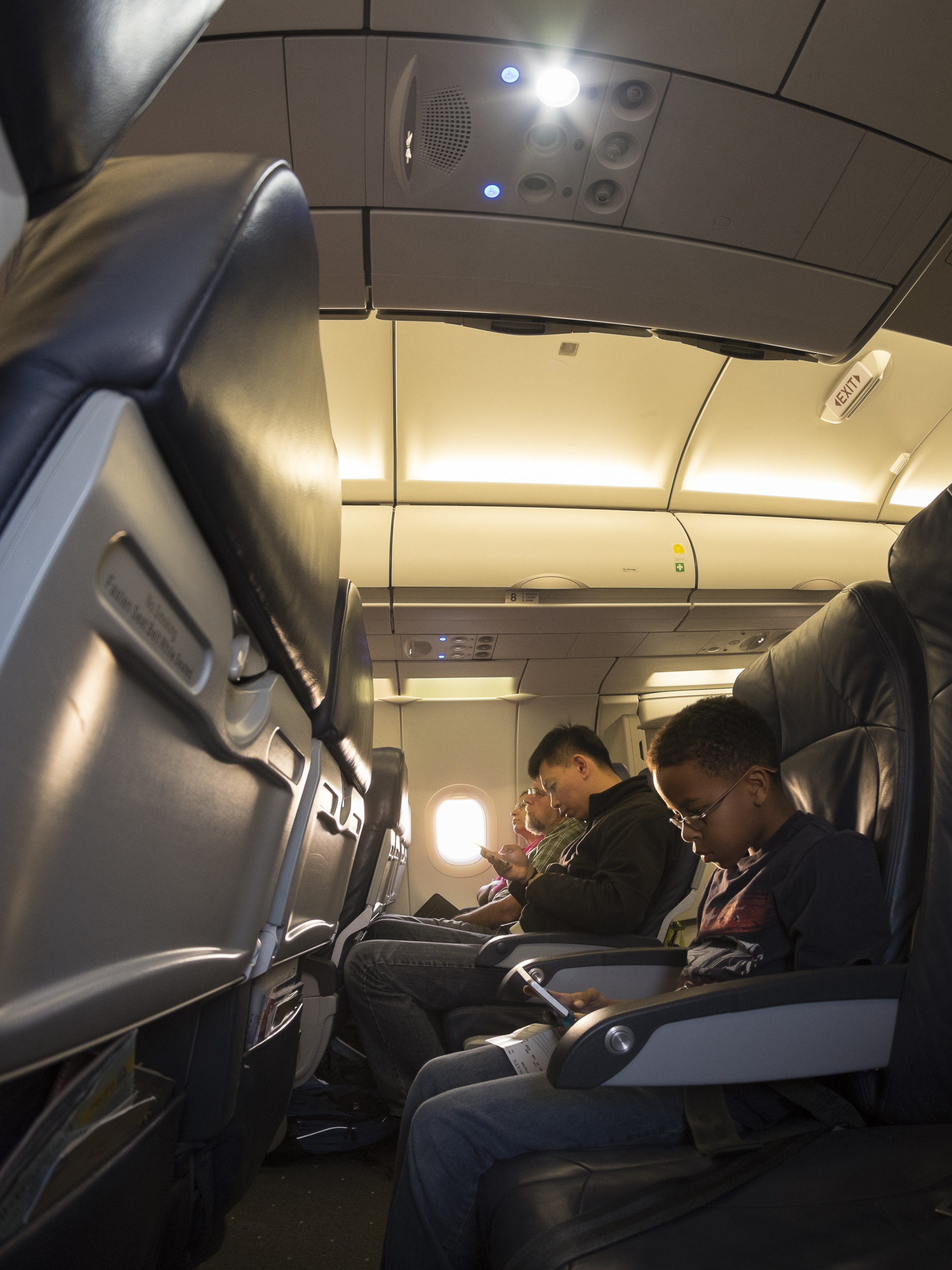 Young traveler concentrates on his mobile device while awaiting takeoff. Copyright © Kipp Baker, All rights reserved.