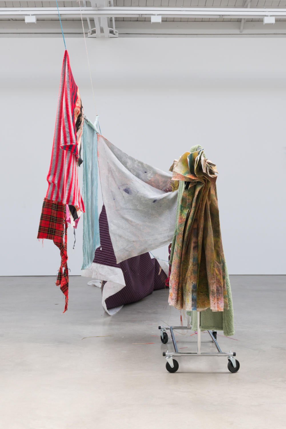 Eric Mack  Come Live With Me Angel  (Alternate view) 2016 Rope, straight pins, acrylic on plush microfiber blankets, polyester fabrics, dye, bleached silk, decorative bouquet, and aluminum clothing rack 94h x 300w x 52d in ENM002