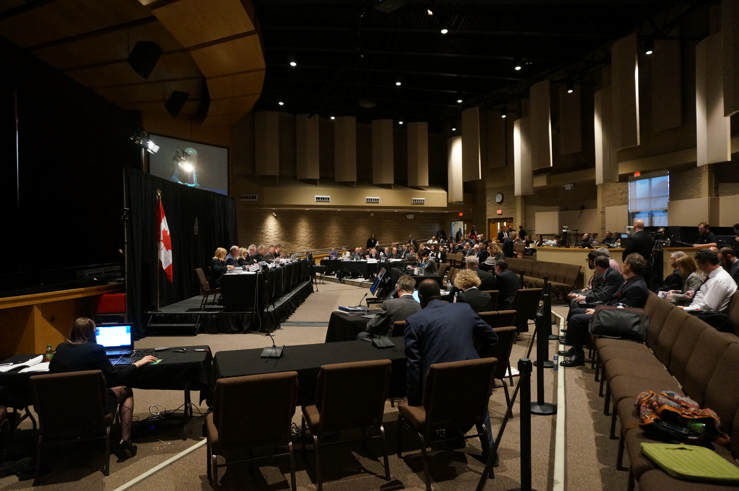 The Commission sitting on the raised stage to the left. OPG representatives, intervenor tables and CNSC staff located in the cordoned off area facing the Commission. (Photo by Lake Ontario Waterkeeper)