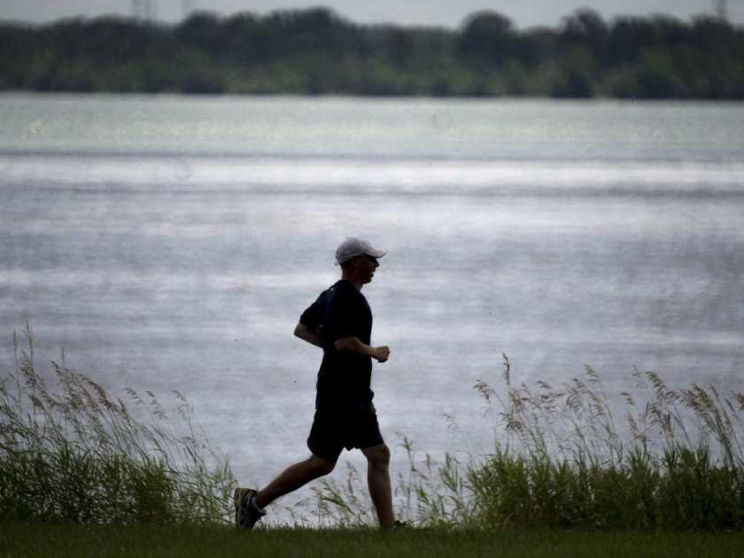 A man jogs along the St. Lawrence River in Montreal on Wednesday, July 9, 2014. The City of Montreal is standing by its plan to dump eight billion litres of untreated wastewater into the St. Lawrence River, saying it remains the best alternative. (Photo by Paul Chiasson / The Canadian Press)