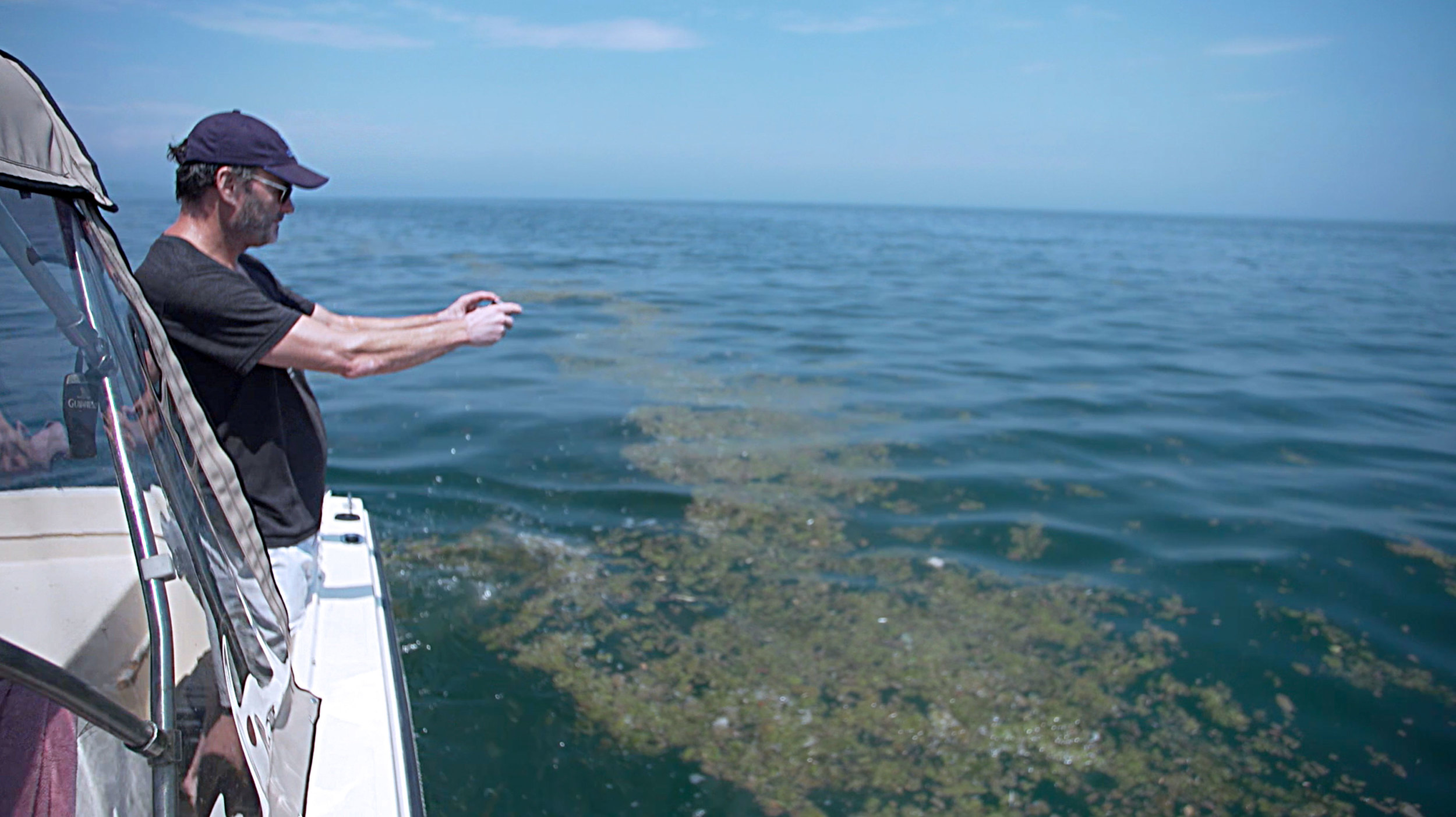 Mark Mattson taking photos of sewage debris while traveling back to Toronto by boat. (Image via Brett Rogers)