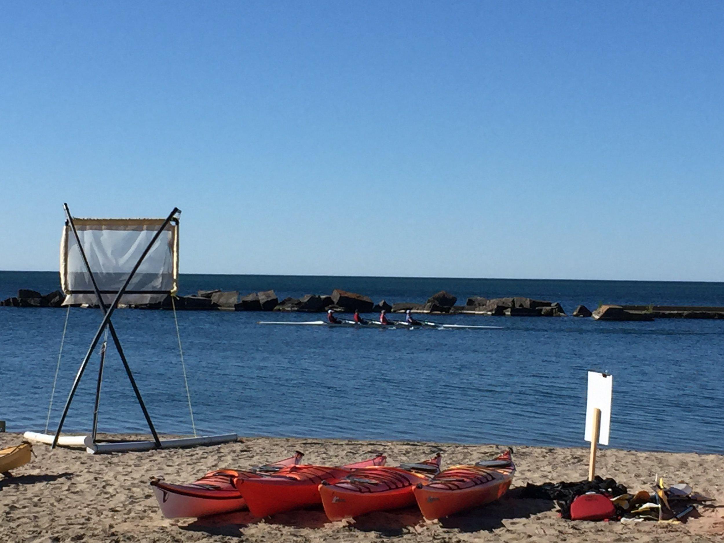 Group of four rowing alongside Sunnyside Beach in Toronto. Photo by Lake Ontario Waterkeeper.