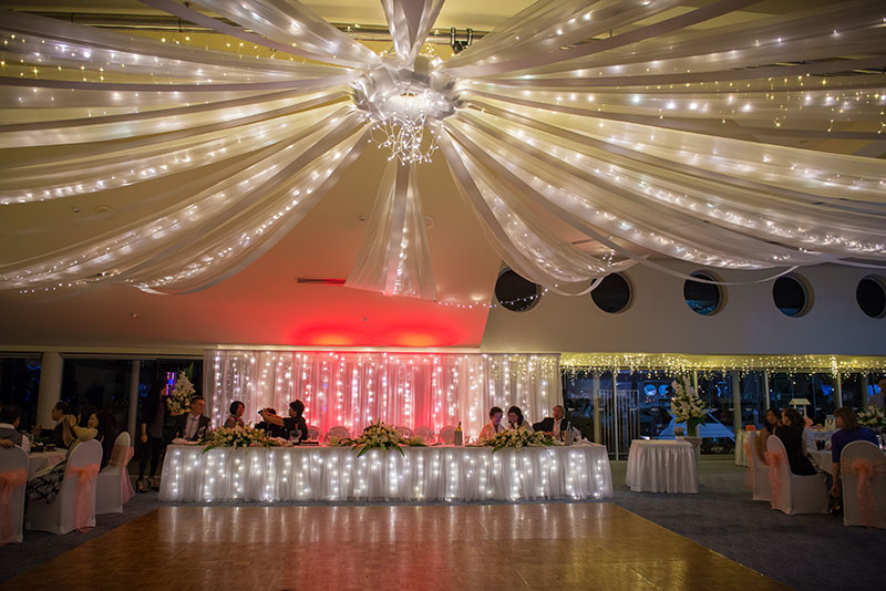 A simple white fabric and fairy light backdrop with coloured lights. The light colour can be changed to suit your colour scheme.