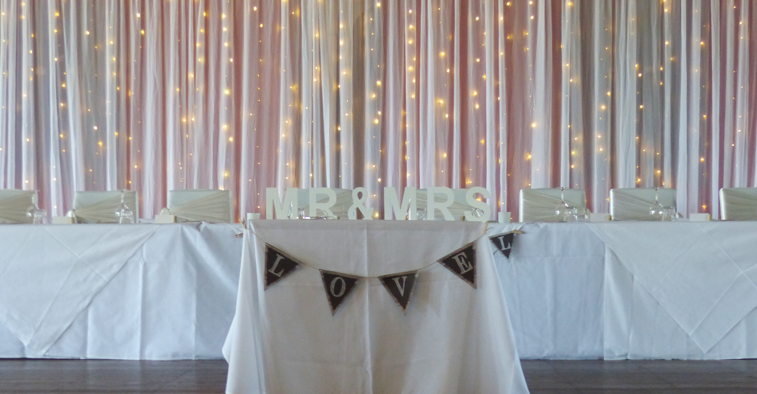 Simple white backdrop with fairy lights.
