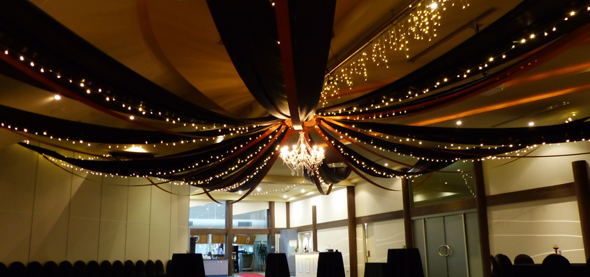 A black and gold Gatsby inspired canopy with large chandelier.