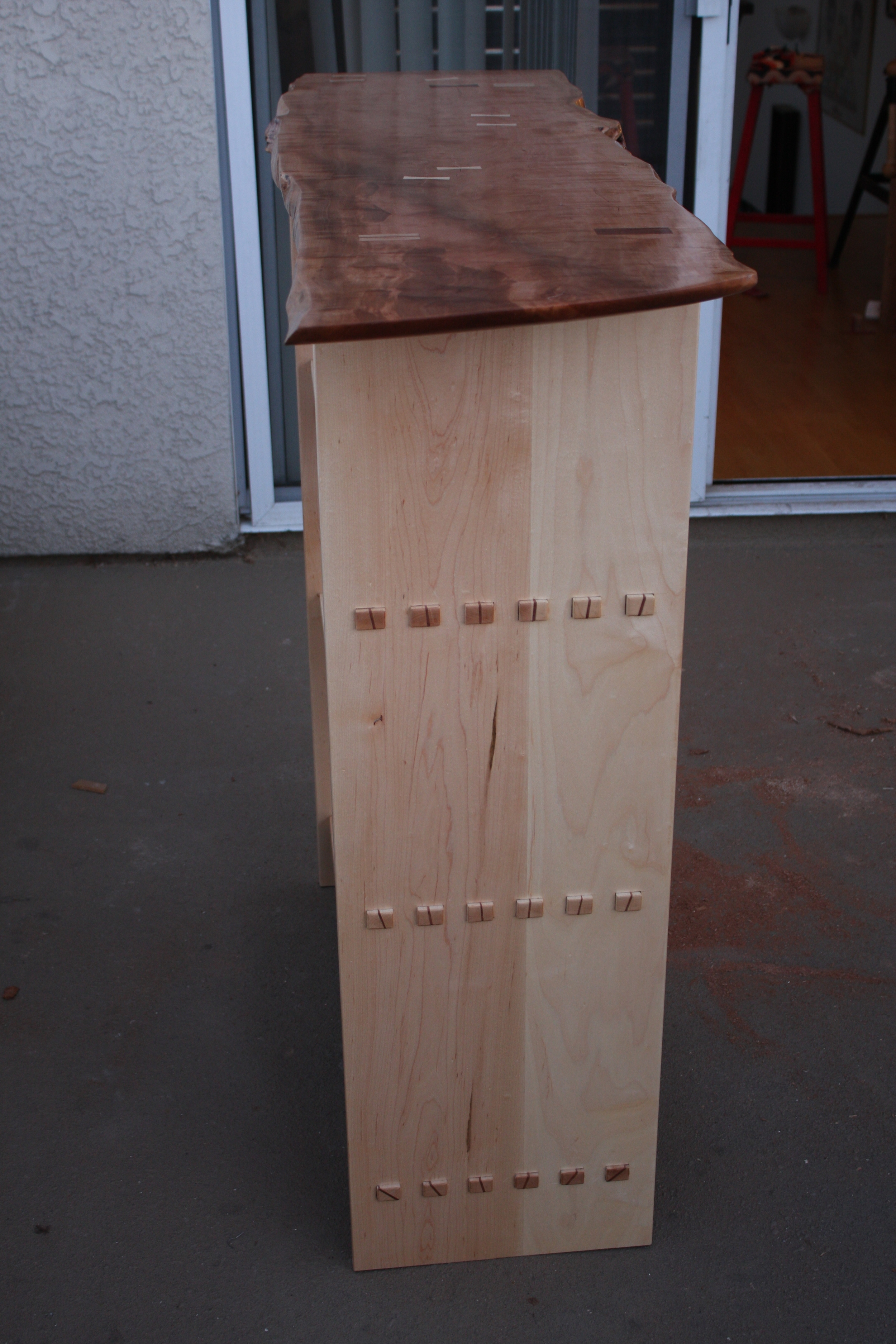The birch is the slightly pinker wood on the left, and the maple is the lighter wood on the right. The slab (top of the shelf)is figured pear.