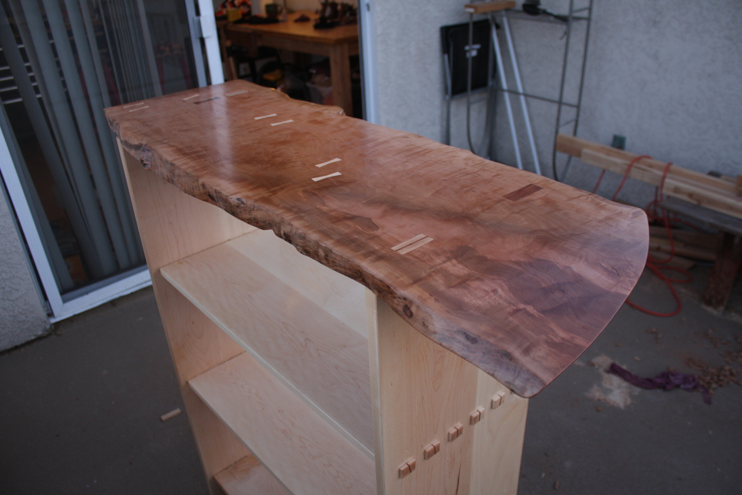 All of the different joints are visible in this picture: dovetail keys to the left, through mortise and tenons (wedged to the right). That rectangular patch is a piece of koa placed over a wedged mortise and tenon joint.