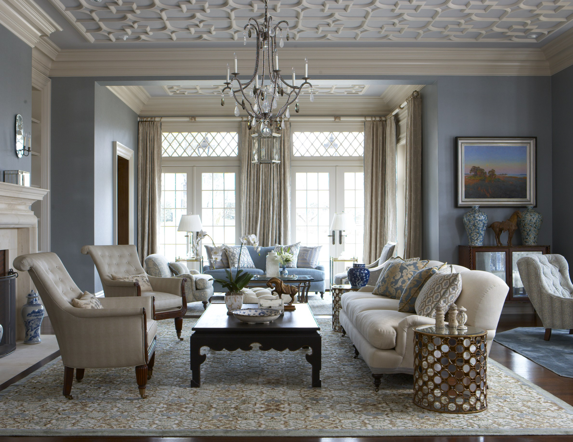 Cindy Rinfret lets the architecture shine in the living room by keeping the furniture understated and by highlighting the beautifully detailed plaster ceiling by painting it cream and blue, with those colors reflected in the luxurious rugs that ground the room. Photo by Michael Partenio.
