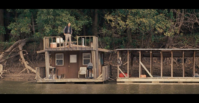 PHOTO CREDIT: Above is a screenshot of Tom Blankenship (Sam Shepard) standing on the roof of his boathouse.