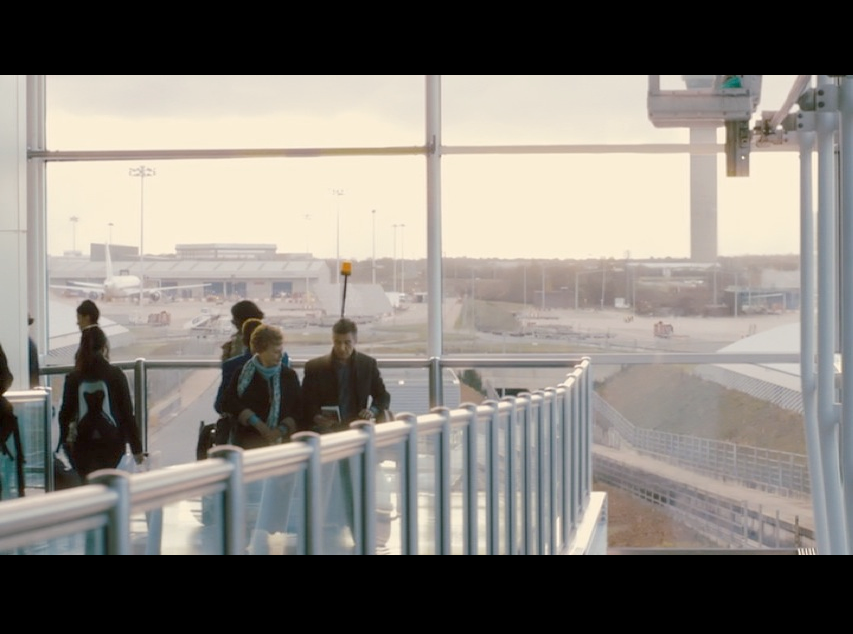 Screenshot from  Philomena  of Martin and Philomena riding on a luggage cart at Stansted Airport. The large floor-to-ceiling windows at the airport provide a beautiful backdrop and much-needed natural lighting for the film set.