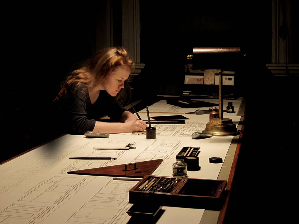 Annie Atkins, the graphic designer for  The Grand Budapest Hotel , hard at work in one of the offices on the upper floor of the Görlitz Warenhaus Department Store. Image via   The Indepent  .