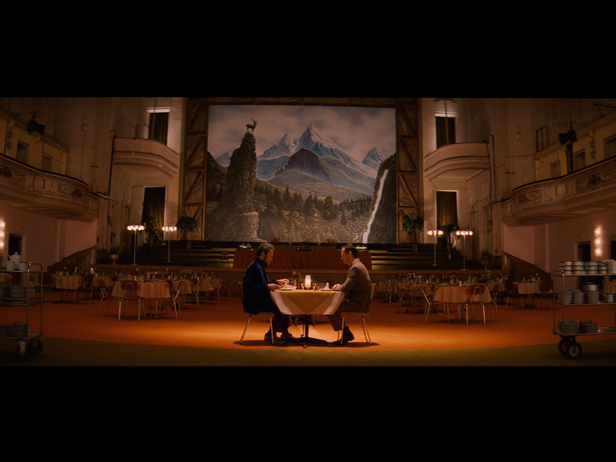 Screenshot from the movie featuring Zero and the Author during their private dinner at the hotel - filmed at the Stadhalle. The giant artwork on the stage behind them is by artist Michael Lenz, in the style of 19th Century landscape artist Caspar David Friedrich.
