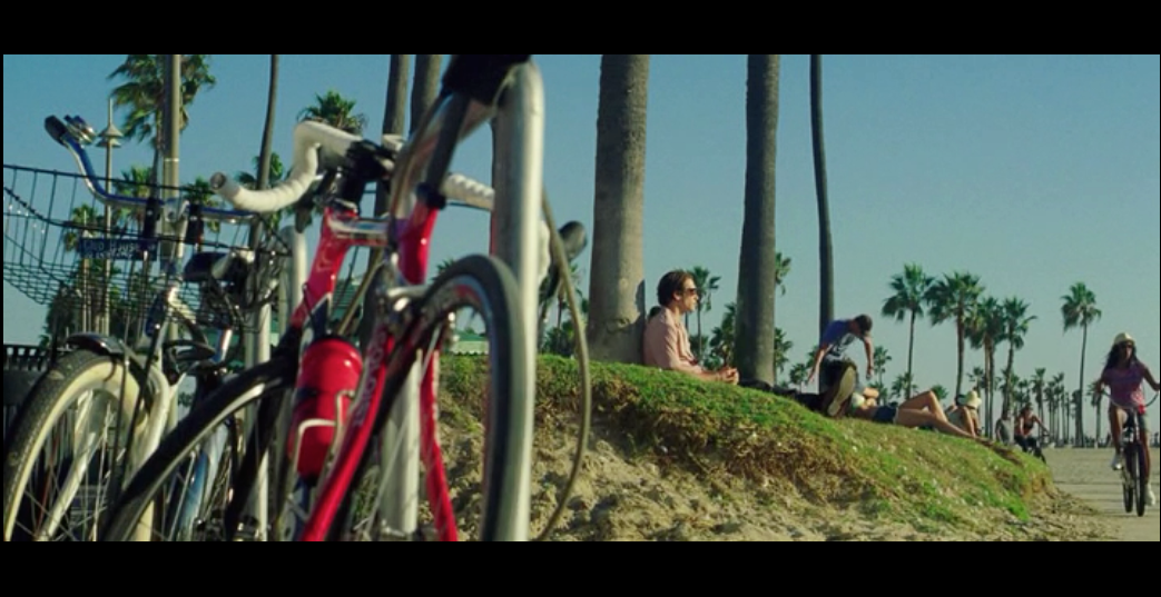 Screenshot from  Nightcrawler  of a scene filmed on the boardwalk of Venice Beach - featuring Lou Bloom sitting under a tree planning a bicycle heist to pawn for video equipment.