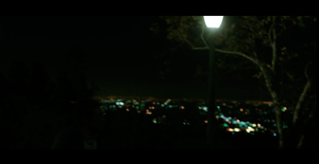 Screenshot from  Nightcrawler  of a scene filmed on Mulholland Drive with the twinkling lights of Los Angeles in the valley below.