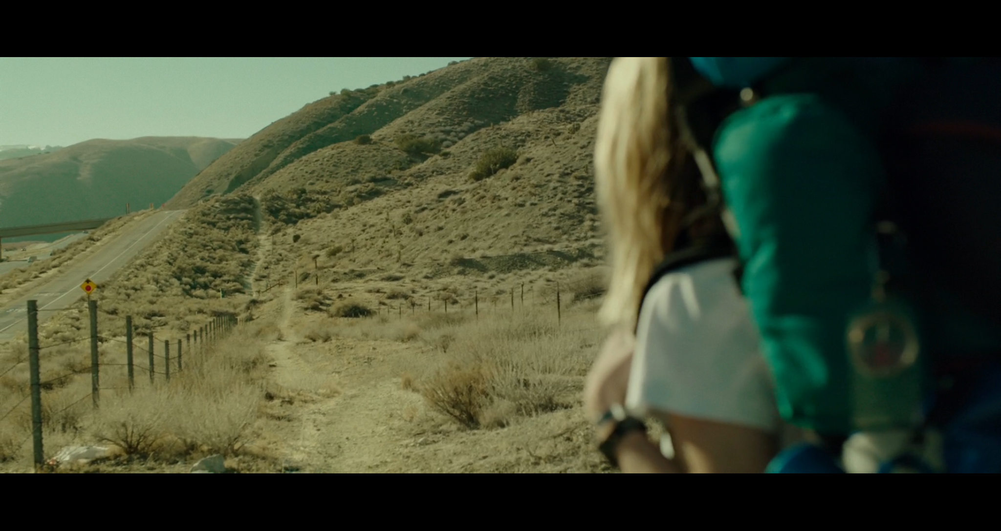 Screenshot from a scene in Wild where Cheryl (Reese Witherspoon) is on the Pacific Crest Trail section near the highway in the Mojave Desert at the beginning of her journey. Filmed on location on the PCT in the Mojave Desert, California.