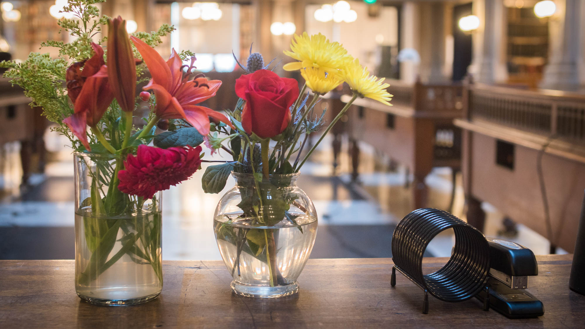On some of the desks in the George Peabody Library, there are vases of fresh flowers.
