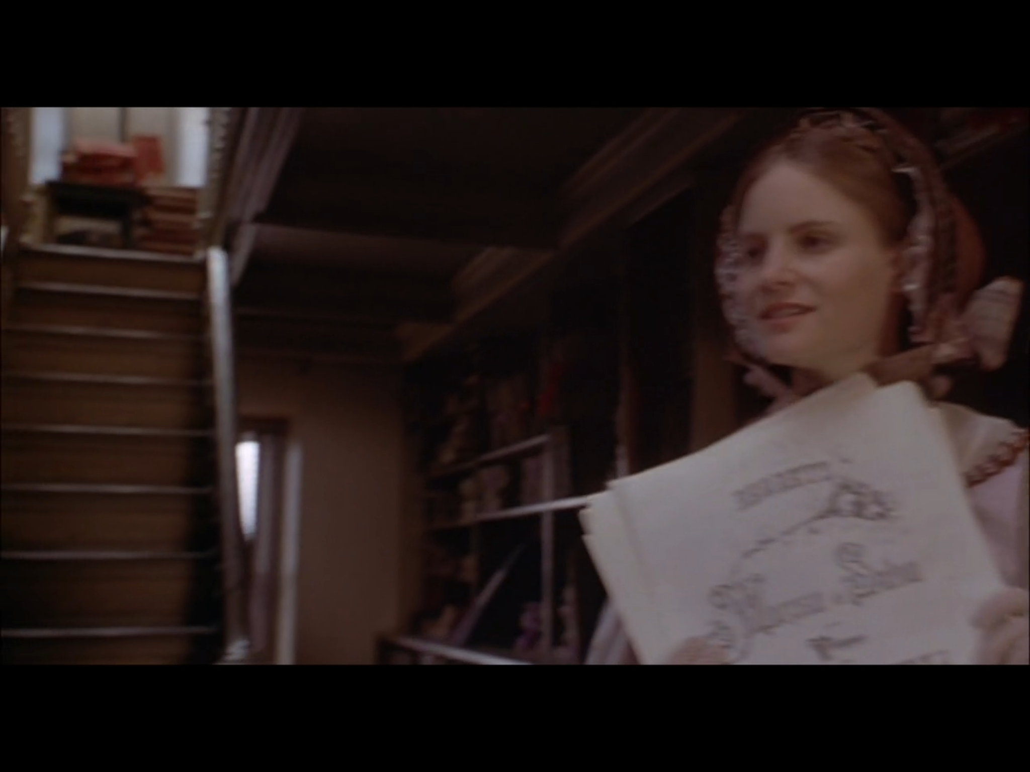 Screenshot from Washington Square of Catherine Sloper (Jennifer Jason Leigh) in a Paris bookshop. This scene was filmed in the George Peabody Library by the stairs leading up to the book stacks above.