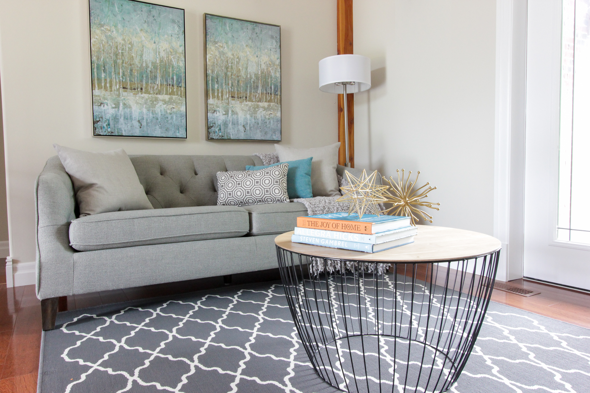 Home Staging provided by New Leaf Decor of living room in Essa- Modern pieces mixed in with colourful art and accents.