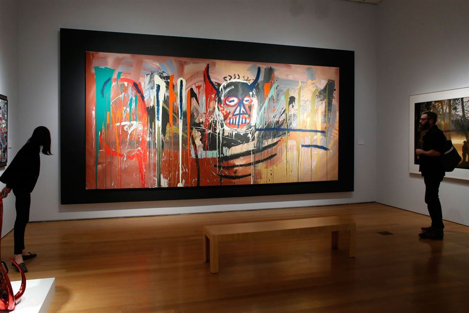 """This monumental self-portrait by Jean-Michael Basquiat set a world auction record for the artist at $57.3 million at a Christie's contemporary art sale on May 10, 2016. Basquiat's self-portrait, """"Untitled, 1982,"""" portrays the young artist as a fiery, demonic figure. The canvas, which features splashes of explosive colors, has appeared in every major Basquiat retrospective. -. (AP Photo/Mary Altaffer, File)THE ASSOCIATED PRESS"""