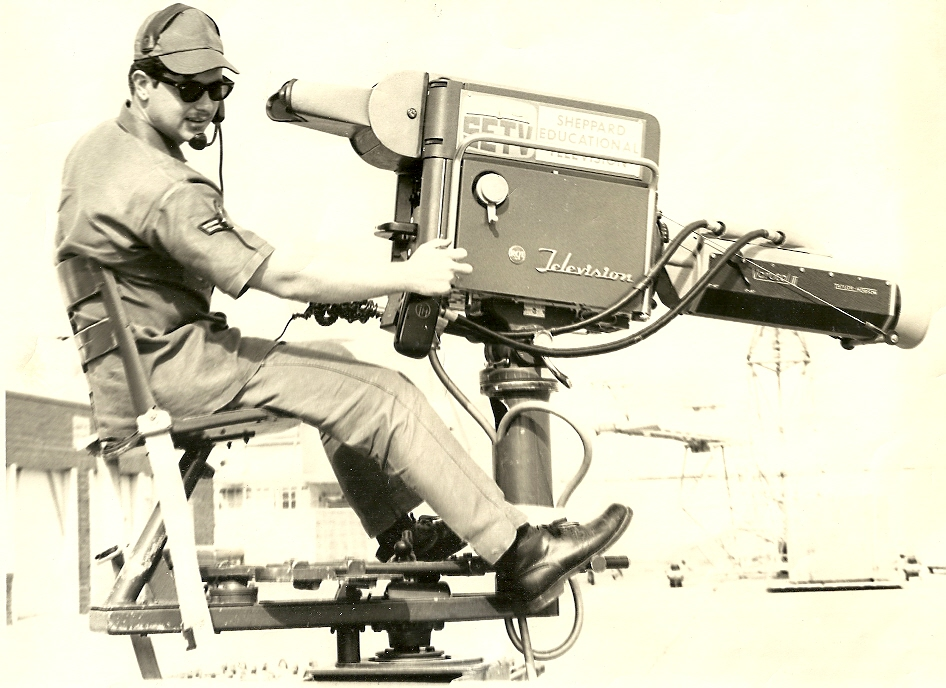 Airman Jaeger in 1969 behind an RCA TK-11 B&W Camera with a Varotal Mark III 400mm zoom lens, mounted on a field boom crane. The base of the mount went from about 5 feet up to 10 feet, and swung about 180°.
