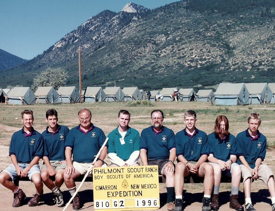 Jim (seated behind the sign to the right) and his crew before backpacking over 50 miles in the Sangre De Cristo mountains at Philmont Scout Ranch near Cimarron, New Mexico, in August 1996.