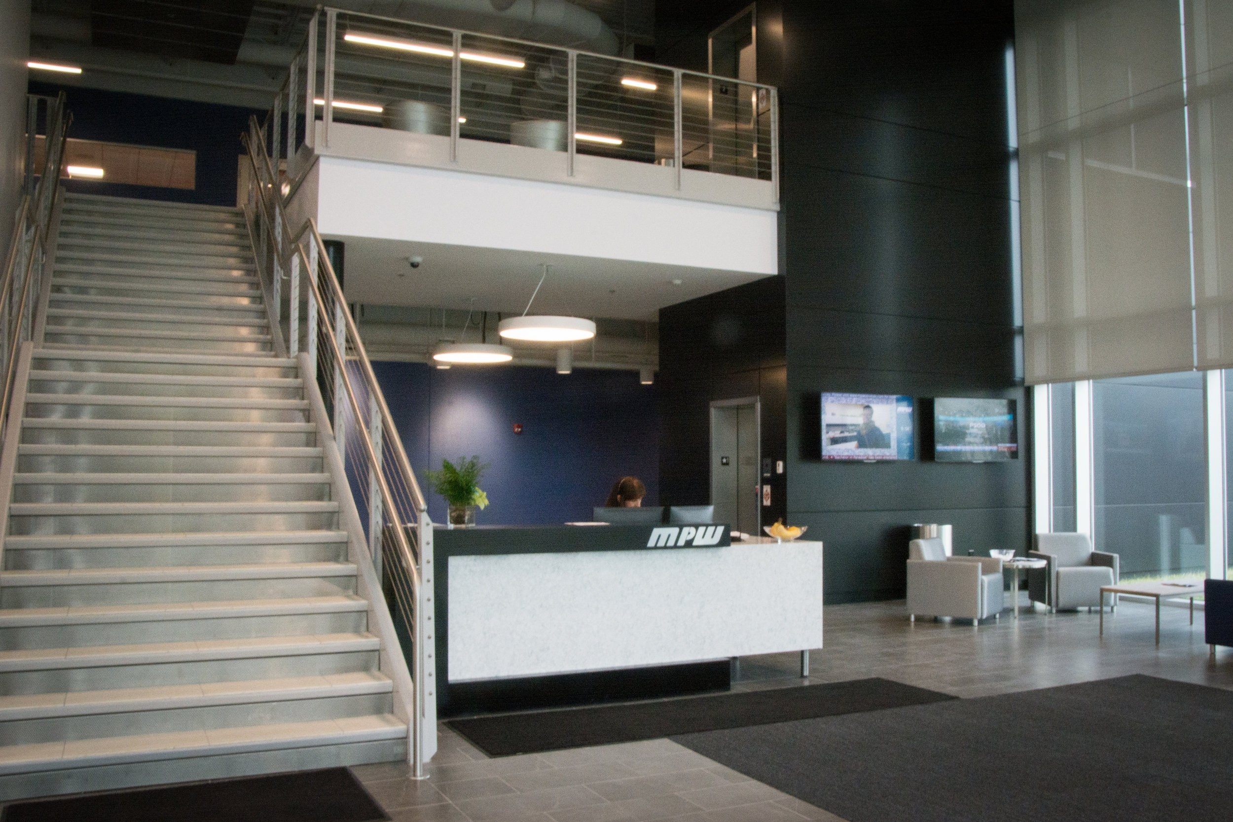 Digital signage and a television greet staff and guests in the bright, open lobby.