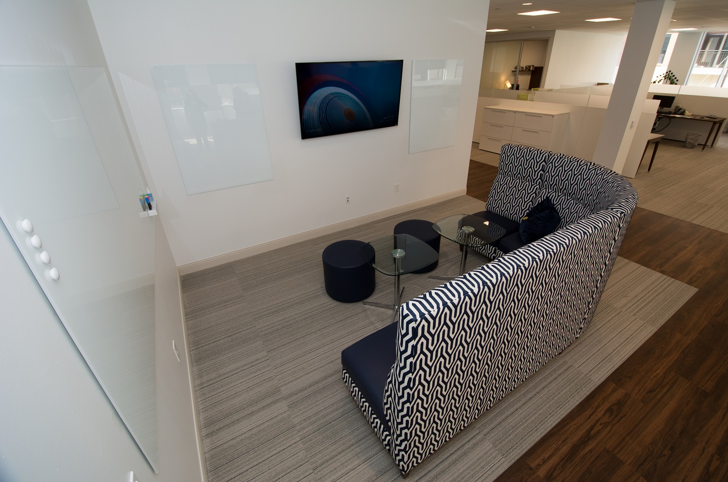 """This huddle space, defined by the extended height of the l-shaped couch, offers multiple whiteboards as well as a variety of inputs for display on the 60"""" TV screen."""