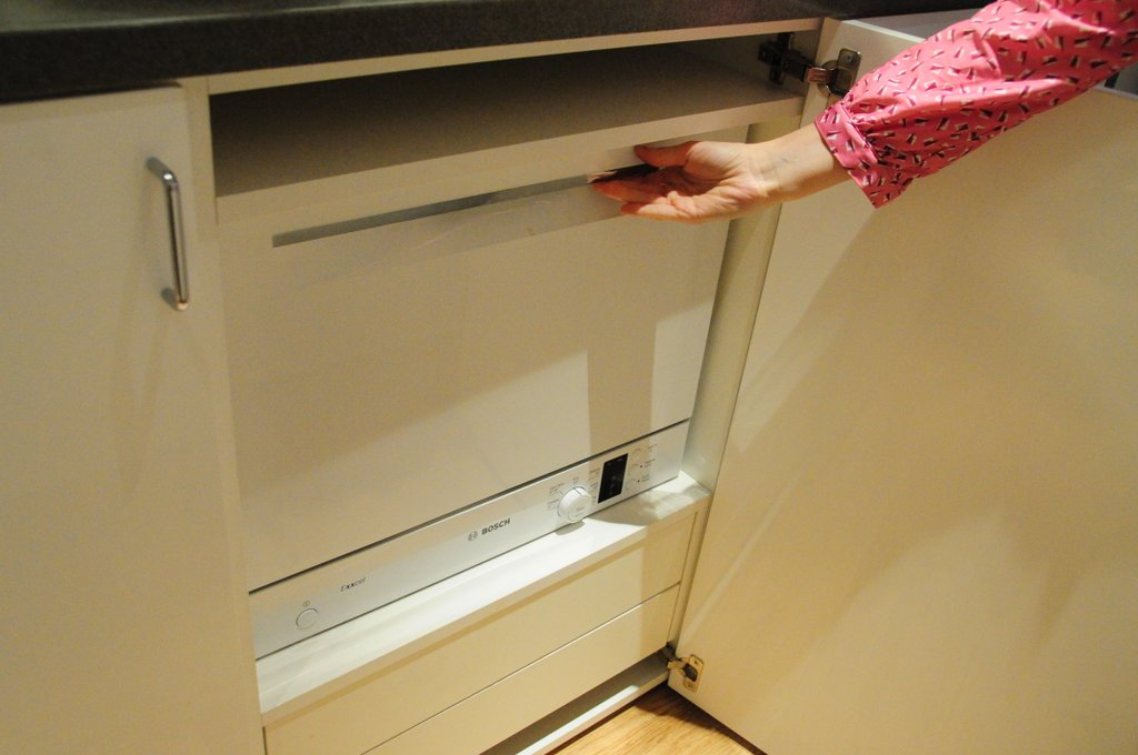 The mini-dishwasher was hidden in a cabinet under the stove top