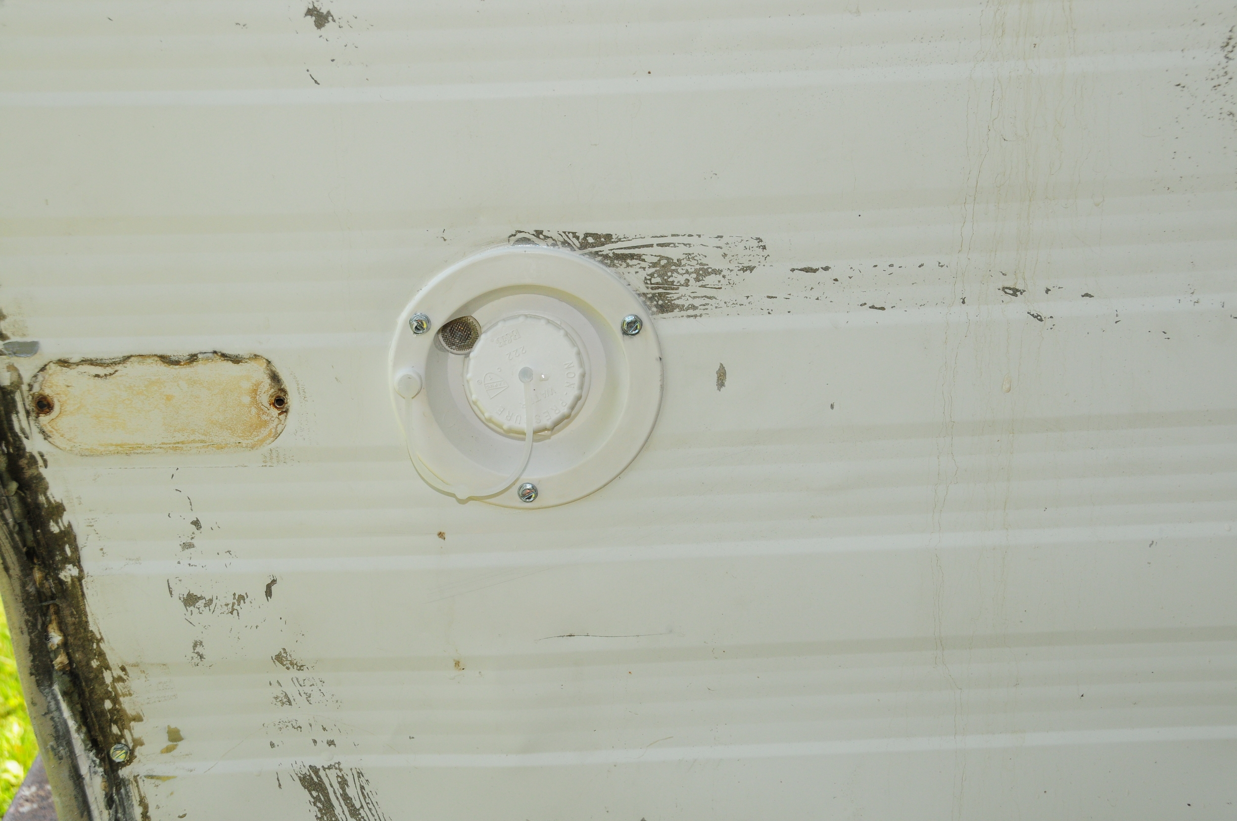 Close up of the fill. We caulked around the edges, and screwed it into the wall. The small spot to the left of the spout is the vent, which allows the tank to empty correctly.