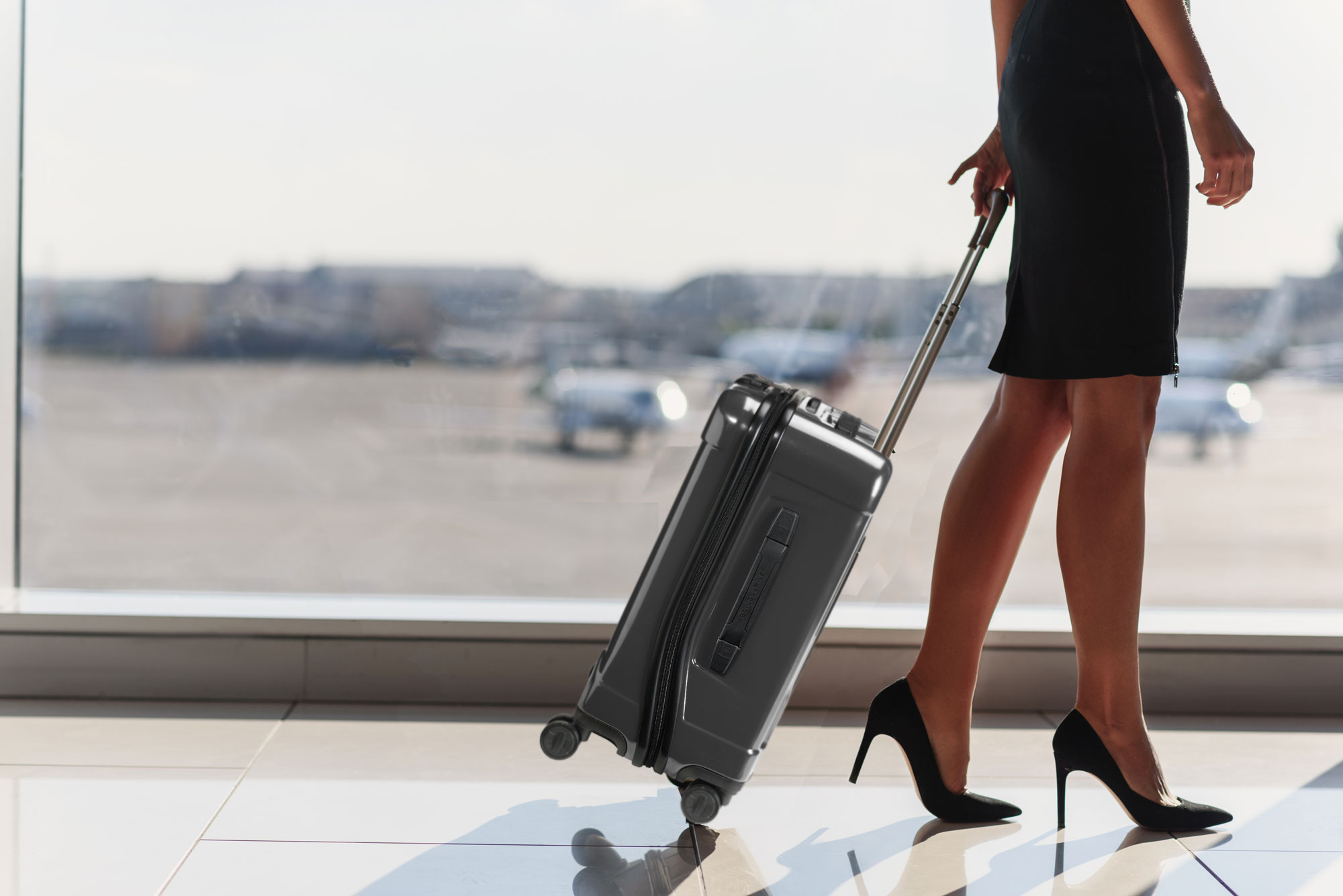 Young-businesswoman-traveling-on-official-journeybriggs_And_riley_torq_carry_on_suitcase.jpg