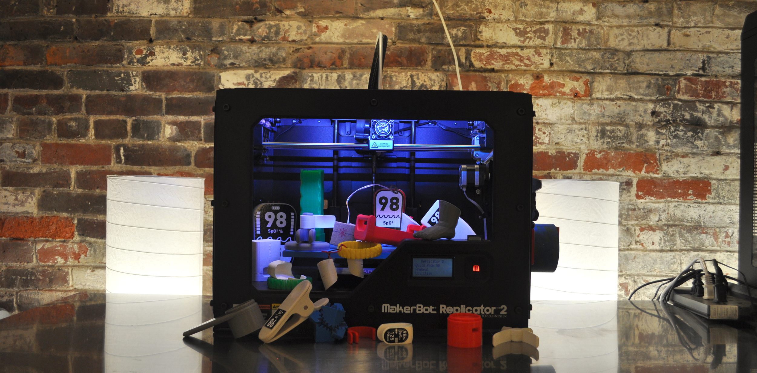 DtM's Makerbot 3D Printer and the pile of prototoypes we've created with it so far.