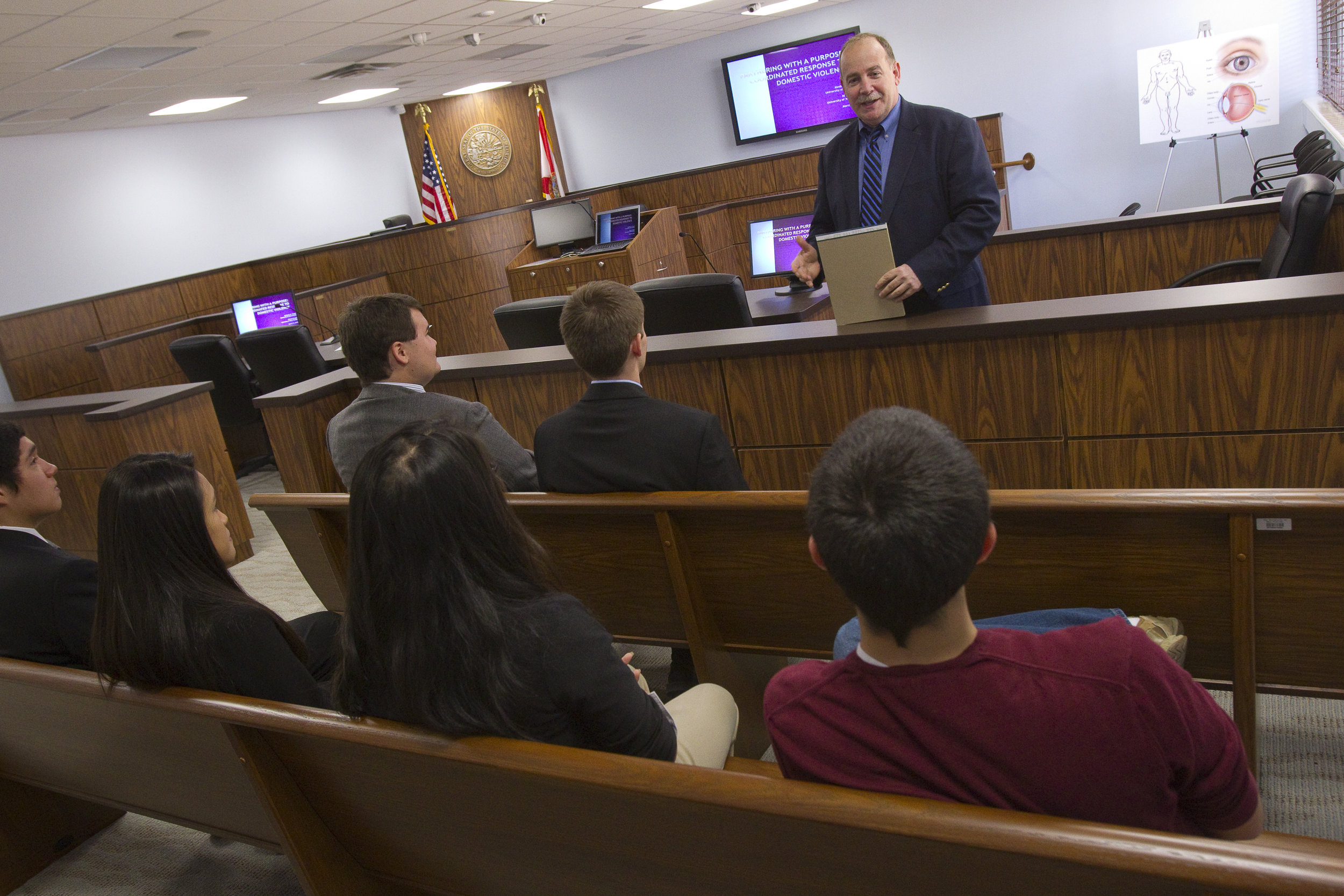 - Dr. Hough discussing expert witness testimony with mock trial team members.