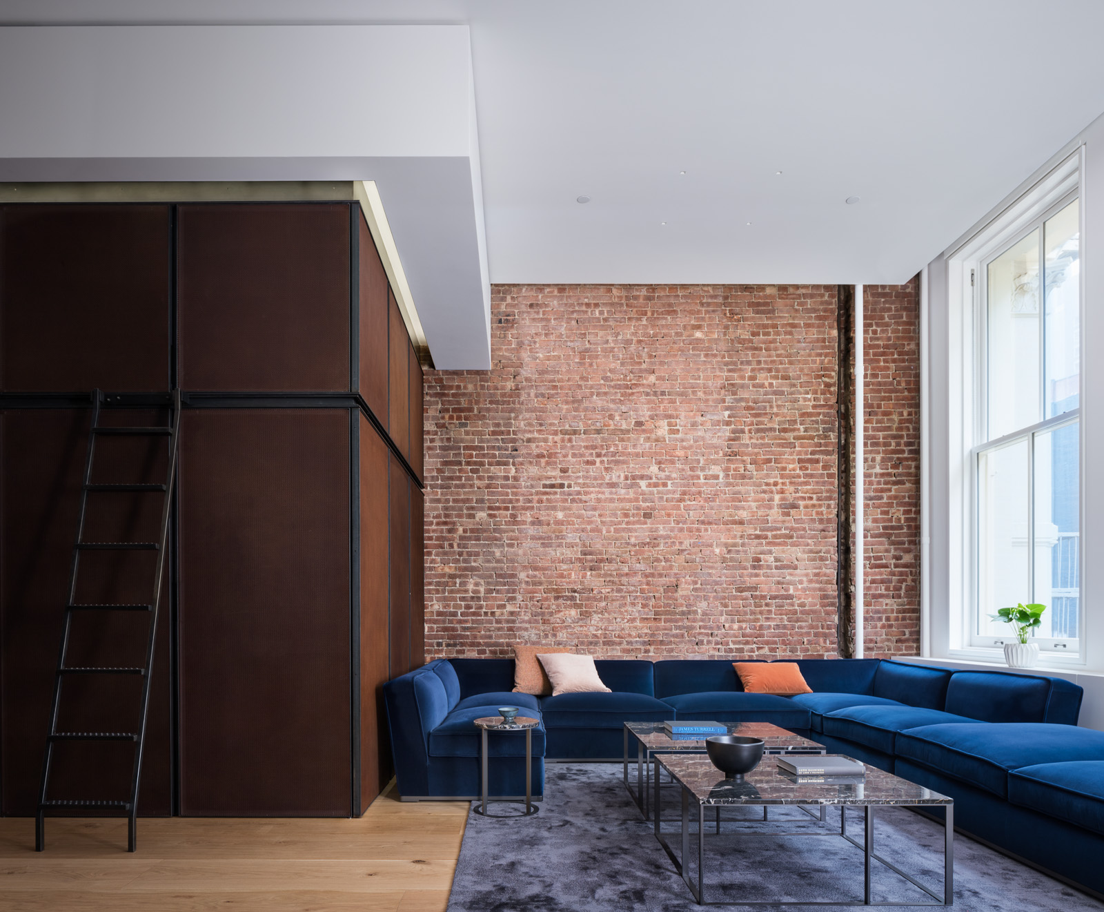 We created a knife edge cove detail that wraps the North, South and West walls. The pocket conceals linear LED grazers that highlight the exposed brick, window treatments and perforated corten steel feature walls.