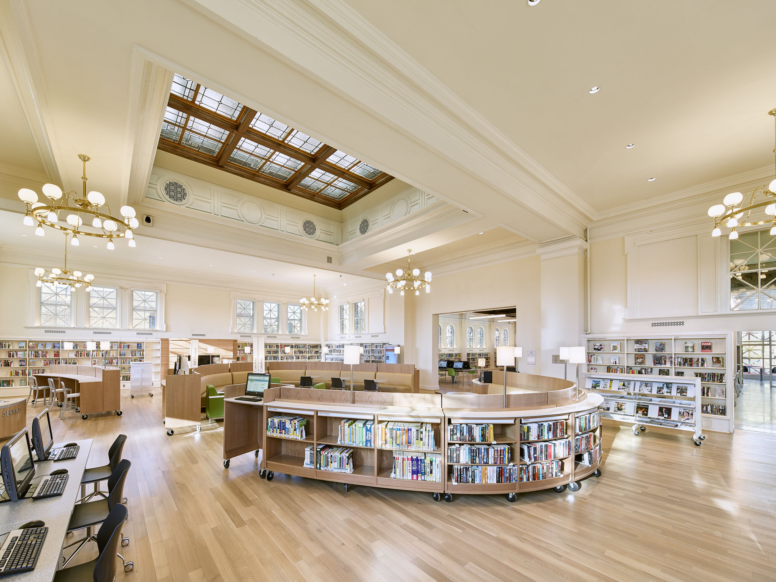 The existing pendants were replaced with versions similar to the original fixtures. Recessed down-lights were added to create more direct light for the readers. Every window is up-lit from the inside sill with a linear LED up-light. This creates the illusion that the library is always open after dark and allows it to act as a lantern and beacon in the neighborhood.