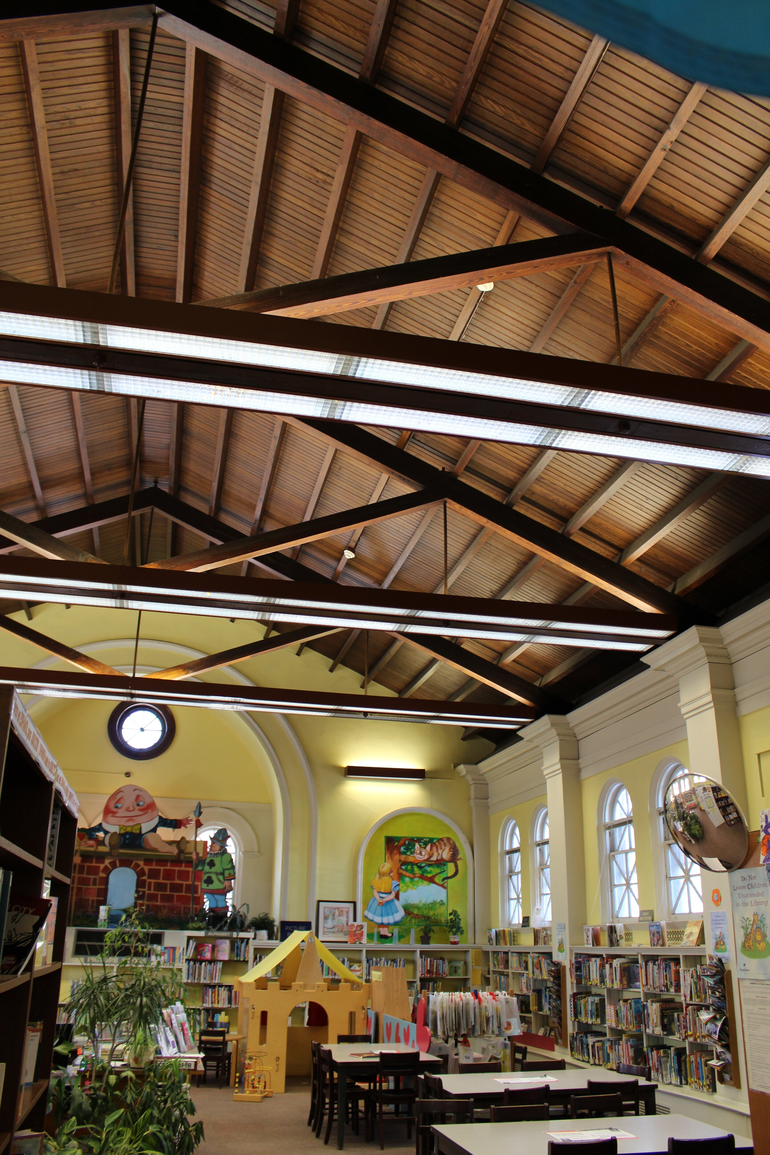 The children's reading room was an addition to the original library. The original lighting scheme included surface mount fluorescent fixtures added above the exposed beams to highlight the ceiling with double rows of surface mount fluorescent lights added below the beams to provide general light.