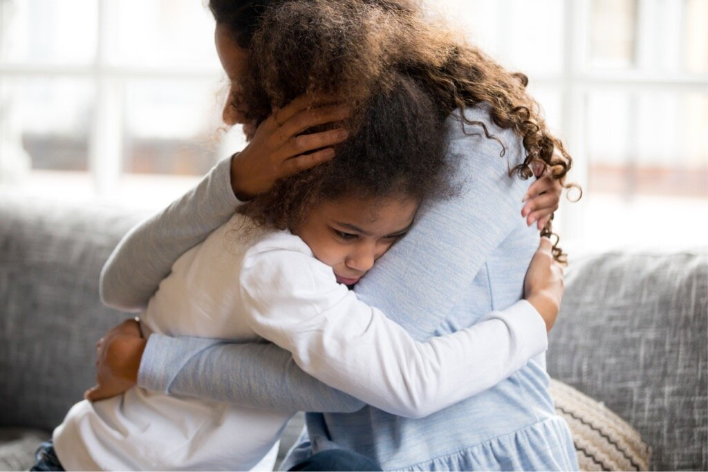 black-mother-and-daughter-embracing-sitting-on-couch-picture-id1051381418.jpg