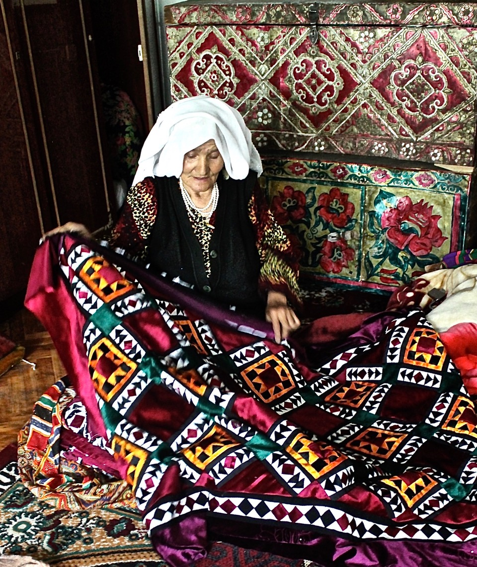 Tajikistan. Woman with quilt of velvet and silks