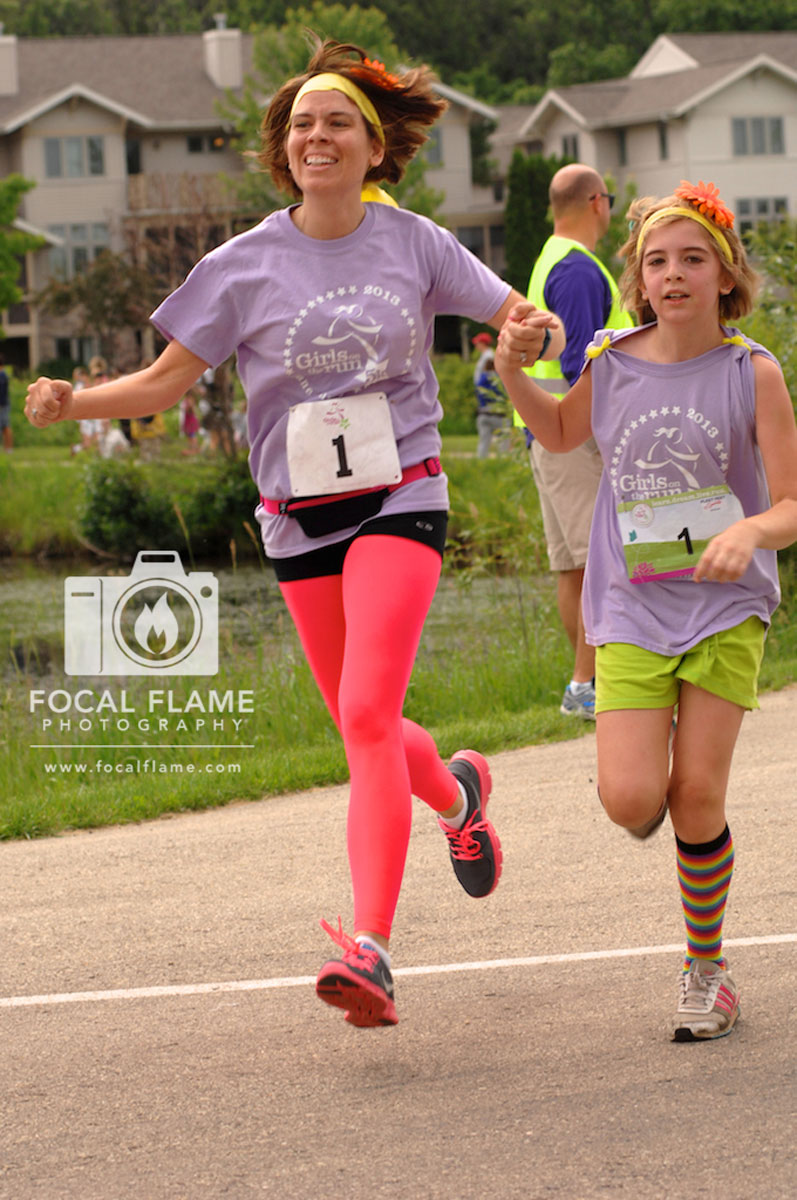 Triumphant runner Krissy Schintgen crosses the finish line of her first 5K alongside her daughter in June, 2013. Photo credit: Katie Richard, Focal Flame Photography