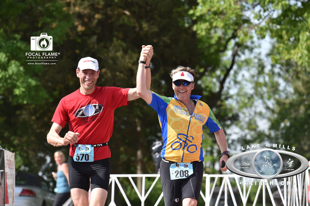 Klaas (left) and Jay (right) cross the finish line of the Lake Mills Triathlon, hand in triumphant hand. (c) 2014 Focal Flame Photography. Photo credit: Clint Thayer
