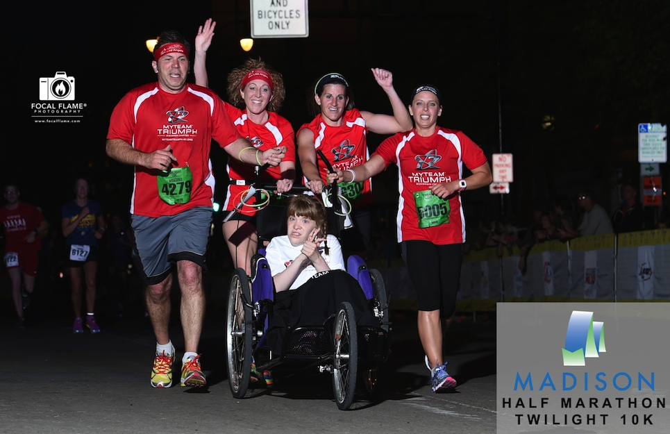 A myTEAM TRIUMPH team approaches the finish line of the 2014 Madison Marathon Twilight 10K. © Focal Flame Photography | Credit: Clint Thayer